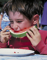boy eating watermelon in watermelon eating contest at outdoor festival. Contest. boy. Mt. Shasta CA USA festival.