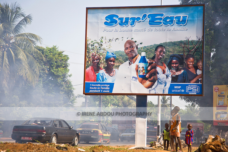Children look up at a billboard advertising Sur'Eau on a busy street through Guinea's capital city of Conakry.  Sur'Eau is a chlorine product that makes water safe to drink and is distributed by the international social marketing organization, Population Services International (PSI).