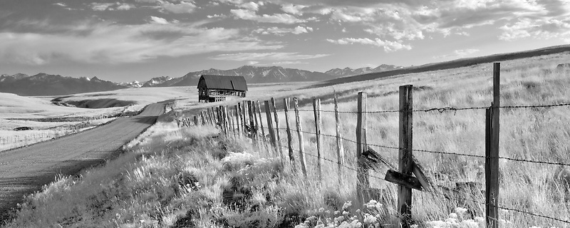 Pasture in Zumwalt Prairie with fence, barn, and Wallowa Mountains, Oregon