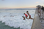 """A group of kids jumps off the Wall at Waikiki. The """"Wall"""" at Waikiki is a favorite place for tourists and locals to hang-out to see the sunrise, sunsets, swim, surf or just to to meet friends."""