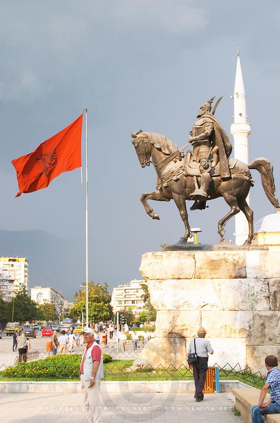 The statue of the 15th century warrior and national hero Skanderburg Skanderbeg on a huge stone base. The red and black Albanian flag. The Tirana Main Central Square, Skanderbeg Skanderburg Square. Tirana capital. Albania, Balkan, Europe.
