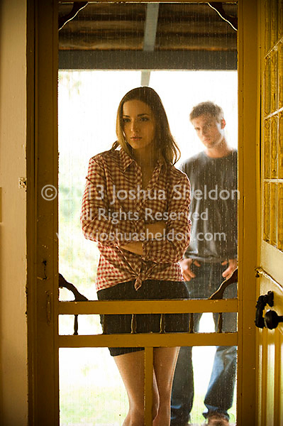 Young woman standing in front of screen door, man seen in background