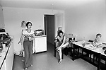 Modern living 1970s working class family life, mother, father and baby who is sitting on the kitchen table in the kitchen of their three bedroom home on a new modern housing development new town Milton Keynes Buckinghamshire England 1977 Note the iron on the wall out of the way behind the woman's head.