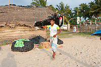 Tamil fisherman shoulders outboard engine -Beruwala fishing village, Sri Lanka