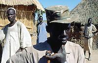 Sudan. South Sudan. Bahr El Ghazal. Wargang. Dinka men in front of family hut whose man was killed by muslim arab raiders from North Sudan during last village attack. © 1999 Didier Ruef