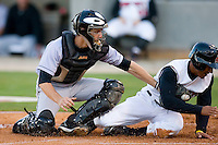 Sean Henry #17 of the Carolina Mudcats slides in ahead of the tag by Brad Davis #6 of the Jacksonville Suns at Five County Stadium May 19, 2009 in Zebulon, North Carolina. (Photo by Brian Westerholt / Four Seam Images)