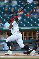 Charlotte Knights designated hitter Eloy Jimenez (20) follows through on his swing against the Rochester Red Wings at BB&T BallPark on May 14, 2019 in Charlotte, North Carolina. The Knights defeated the Red Wings 13-7. (Brian Westerholt/Four Seam Images)