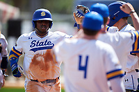 South Dakota State Jackrabbits first baseman Josh Kutzke (25) high fives teammates after scoring a run during a game against the FIU Panthers on February 23, 2019 at North Charlotte Regional Park in Port Charlotte, Florida.  South Dakota State defeated FIU 4-3.  (Mike Janes/Four Seam Images)