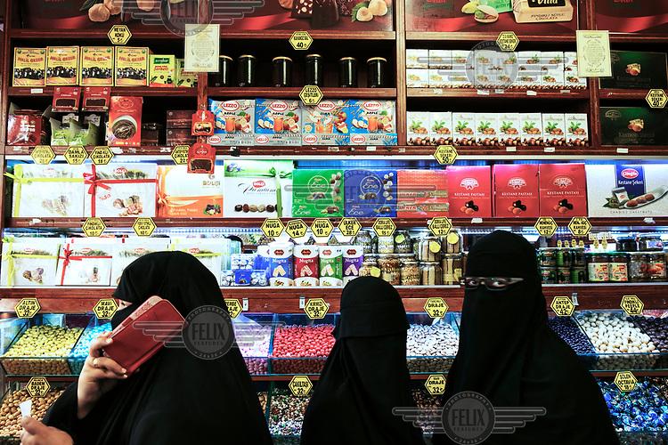 Women wearing niqabs inside a sweet shop in the central market.