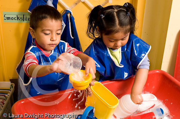 Education preschool water table a boy and a girl playing side by side at water table horizontal