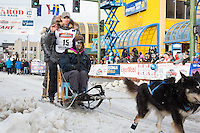 Matt Failor and team leave the ceremonial start line with an Iditarider at 4th Avenue and D street in downtown Anchorage, Alaska during the 2015 Iditarod race. Photo by Jim Kohl/IditarodPhotos.com