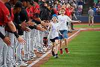 """10 year old Ava Bogniard and 8 year old Liam Young high five players as they run the bases during an Akron RubberDucks Eastern League game against the Erie SeaWolves on August 30, 2019 at Canal Park in Akron, Ohio.  Akron wore special jerseys with the slogan """"Fight Like a Kid"""" during the game for Akron Children's Hospital Home Run for Life event, the design was created by 11 year old Macy Carmichael.  Erie defeated Akron 3-2.  (Mike Janes/Four Seam Images)"""