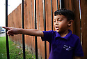 Christopher Mejia points to his father's car from the gate of his grandmother's home in Metairie, La. He misses his father, Erlin San Martin, who has been detained by immigration authorities.