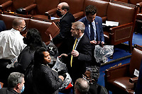 House of Representatives members leave the floor of the House chamber as protesters try to break into the chamber at the U.S. Capitol on Wednesday, Jan. 6, 2021, in Washington. Rep. Jim Jordan, R-Ohio, is at center. (AP Photo/J. Scott Applewhite)