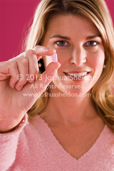 Young blonde Caucasian woman holding pill