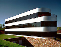 Exterior profile view of the modernistic, oblong architecture of a contemporary office building.