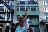 A protestor gives a thumbs up to supporters cheering from their window during a march in Washington, D.C., U.S., on Monday, June 1, 2020, following the death of an unarmed black man at the hands of Minnesota police on May 25, 2020.  More than 200 active duty military police were deployed to Washington D.C. following three days of protests.  Credit: Stefani Reynolds / CNP/AdMedia