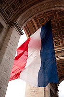 The French national flag blowing in the wind underneath the famous landmark the Arc De Triomphe, Paris, France