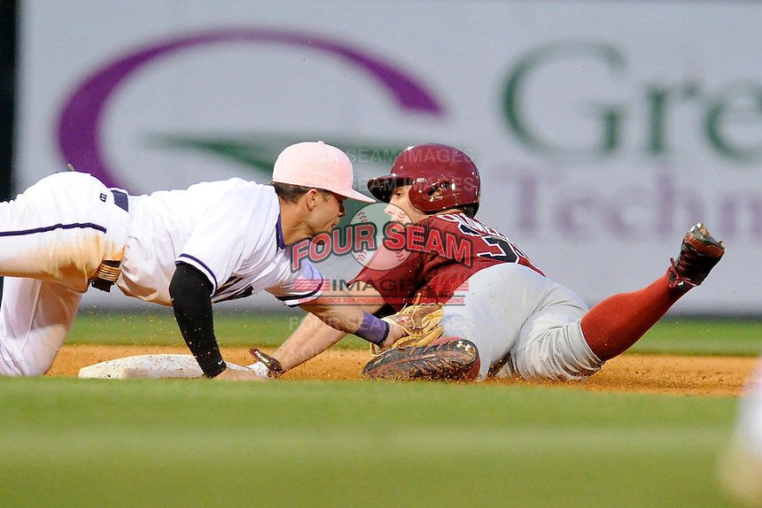 Left fielder Elliott Caldwell (30) of the South Carolina Gamecocks is out at second as shortstop Hunter Burton (1) of the Furman Paladins applies the tag in a game on Tuesday, April 8, 2014, at Fluor Field at the West End in Greenville, South Carolina. South Carolina won, 9-2. (Tom Priddy/Four Seam Images)