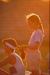 girl braiding woman's hair