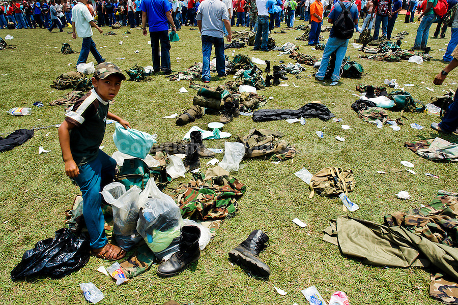 A young Colombian boy searching for the army gear after the demobilization ceremony of the AUC paramilitary forces, Meta Department, Colombia, 10 April 2006.