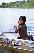 Bacaja village, Brazil. An Indian boy with a fishing line in a boat on the river, Xicrin Indian tribe, Amazon.