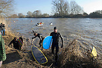 Surfers leaving the water having missed the Severn Bore near Newnham, Glos in the early morning sunshine. The bore was five star rated, which means the biggest of the year, fueled by the large spring tides that push up the River Severn Estuary..