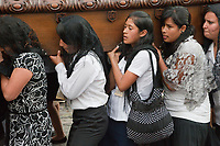Antigua, Guatemala.  Semana Santa (Holy Week).  Strain shows on the faces of women carrying an anda (float) in a procession during Holy Week.