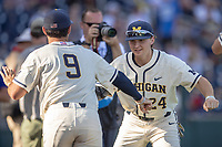 Michigan Wolverines catcher Casey Buckley (24) shakes hands with teammate Matthew Schmidt (9) before playing against the Vanderbilt Commodores during Game 1 of the NCAA College World Series Finals on June 24, 2019 at TD Ameritrade Park in Omaha, Nebraska. Michigan defeated Vanderbilt 7-4. (Andrew Woolley/Four Seam Images)