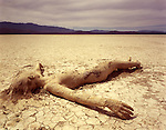 Naked woman lying down in the dirt, and covered in dried mud. Black Rock Desert, Nevada.