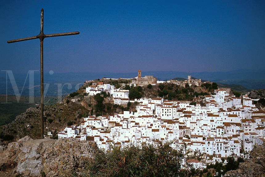Whitewashed village on a hill, metal cross left foreground. Casares Andalucia Spain