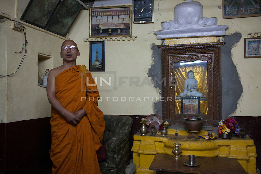 A Buddhist holy man stands in front of the Buddha statue in a temple in Bhaktapur, near Kathmandu, Nepal. May 04, 2015