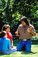 Cherokee storyteller talks with two young members of the nation.  Tahlequah, OK