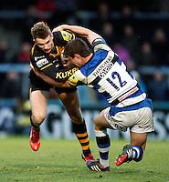 Photo: Richard Lane/Richard Lane Photography. London Wasps v Bath Rugby. Aviva Premiership. 24/11/2013. Wasps' Josh Bassett is tackled by Bath's Ollie Devoto.