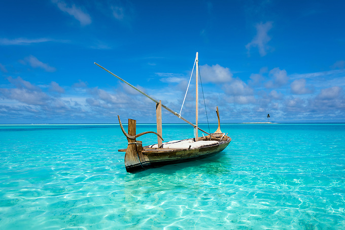 A longtail rests in the shallow emerald waters of the Indian Ocean.