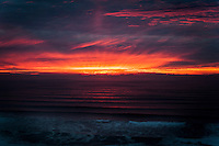 The setting sun fires the clouds red and orange, and their glow is reflected in the rippling waves of the Pacific Ocean along the California coast.