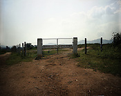 The gate leading to the Ash pond of Vedanta Alumina Company is seen in Lanjigarh, Orissa. Seen at the distance are the Niyamgiri hills.