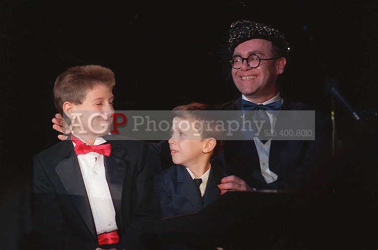 """Jul 09, 1988 - Los Angeles, California, United States - Singer Elton John is joined by Ryan White, left, and Jason Robertson, both suffering from AIDS July 9, 1988 as he performs at """"For The Love of Children,"""" a benefit for children with AIDS, and other serious illnesses or problems, at the Century Plaza Hotel in Los Angeles, July 9, 1988.  John appeared on  stage for the first time in two years..(Credit Image: © Alan Greth)"""