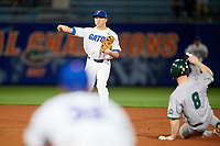 Florida Gators second baseman Blake Reese (12) throws to first base as Dan Lowndes (8) slides in during a game against the Siena Saints on February 16, 2018 at Alfred A. McKethan Stadium in Gainesville, Florida.  Florida defeated Siena 7-1.  (Mike Janes/Four Seam Images)