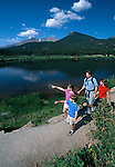 A family hiking on trail around Lily Lake in Rocky Mtn Nat'l Park, CO.