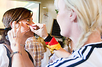 Annette Mansfield applies the German colors to Casey Finnegan's cheeks at Zum Schneider's, a German beer hall in New York City,  before their team's game against Costa Rica on June 9, 2006. <br /> <br /> The World Cup, held every four years in different locales, is the world's pre-eminent sports tournament in the world's most popular sport, soccer (or football, as most of the world calls it).  Qualification for the World Cup is open to any country with a national team accredited by FIFA, world soccer's governing body. The first World Cup, organized by FIFA in response to the popularity of the first Olympic Games' soccer tournaments, was held in 1930 in Uruguay and was participated in by 13 nations.    <br /> <br /> As of 2010 there are 208 such teams.  The final field of the World Cup is narrowed down to 32 national teams in the three years preceding the tournament, with each region of the world allotted a specific number of spots.  <br /> <br /> The World Cup is the most widely regularly watched event in the world, with soccer teams being a source of national pride.  In most nations, the whole country is at a standstill when their team is playing in the tournament, everyone's eyes glued to their televisions or their ears to the radio, to see if their team will prevail.  While the United States in general is a conspicuous exception to the grip of World Cup fever there is one city that is a rather large exception to that rule.  In New York City, the most diverse city in a nation of immigrants, the melting pot that is America is on full display as fans of all nations gather in all possible venues to watch their teams and celebrate where they have come from.