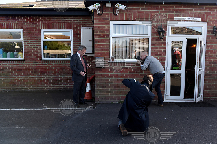 The Sky news team film UKIP leader Nigel Farage as he takes a cigarette break after a photocall during election campaigning on St George's Day, in Ramsgate, Kent.