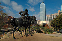 Statue of a cowboy looking skyscraper in Dallas downtown, Texas, USA, United States. The statue is locating by the Dallas Convention Center at the intersection of South Griffin and Young Street. Pioneer Plaza honors Dallas' cowboy past by celebrating the trails that brought settlers to Dallas.