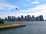American Flag on tip of Ellis Island with New York City skyline in the background.