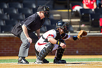 Cincinnati Bearcats catcher Woody Wallace (10) sets a target as home plate umpire Roger Kinley looks over his shoulder during the game against the Radford Highlanders at Wake Forest Baseball Park on February 22, 2014 in Winston-Salem, North Carolina.  The Highlanders defeated the Bearcats 6-5.  (Brian Westerholt/Four Seam Images)