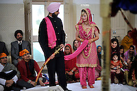 The wedding ceremony of British/Punjabi couple Lindsay and Navneet Singh at a gurdwara in Amritsar. Navneet holds a sword and Lindsay holds a pink scarf which will be tied to them both.