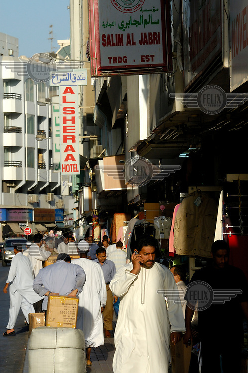 Man using his mobile phone while he walks through the souk..