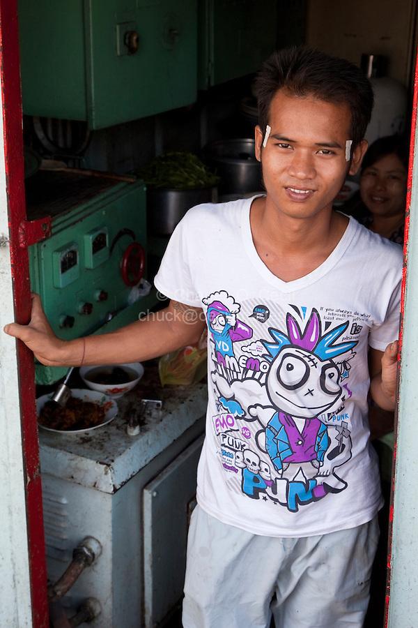 Myanmar, Burma, Yangon.  Boat's Cook Wearing Punk T-Shirt.