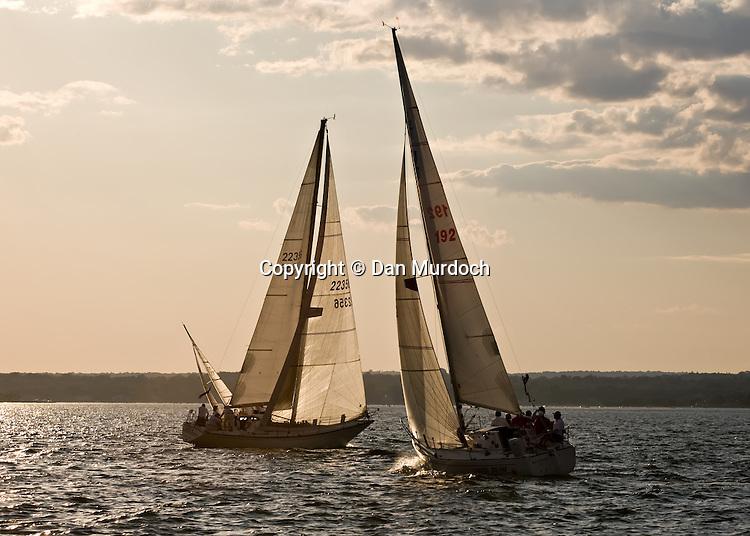 Racing sailboats tacking into the sunset