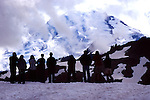 Group of hikers waits for Mt. Baker to emerge from North Cascade Mountain fog and clouds in July at Artist's Point.